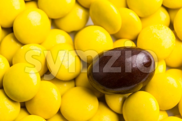 Concept of selective focus on brown chocolate candy against heaps of yellow candies in background