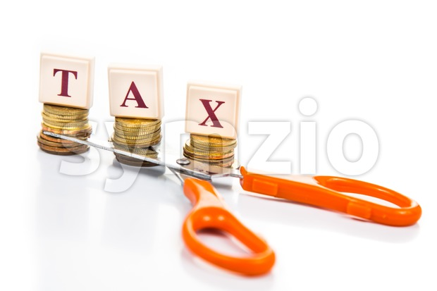Cut taxes concept with coins, words and scissors Stock Photo
