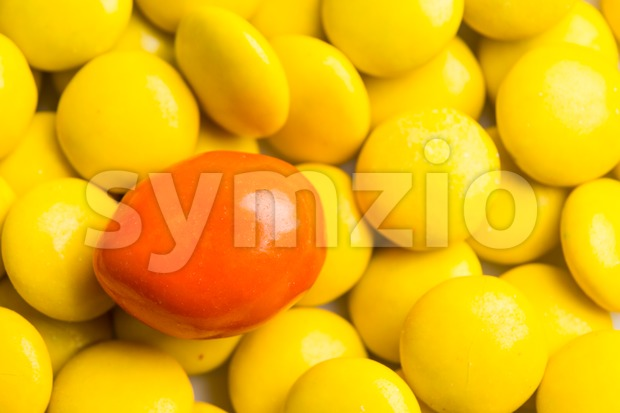Focus on orange chocolate candy against heaps of yellow candies Stock Photo