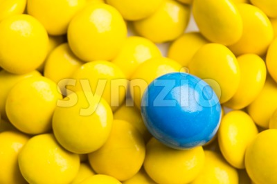 Focus on blue chocolate candy against heaps of yellow candies Stock Photo