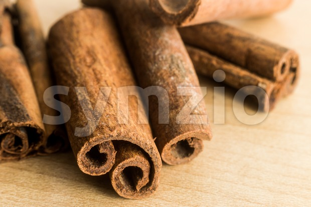 Close up and selective focus on the edge of Cinnamon sticks, on wooden surface Stock Photo