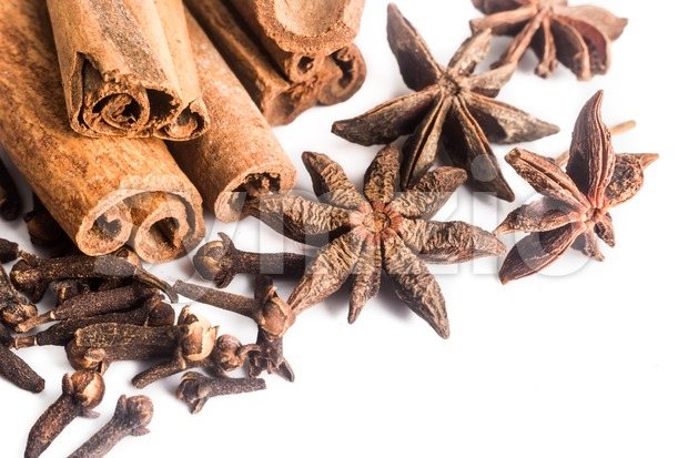 Group of popular spices consisting Cinnamon sticks, Cloves and Star Anise on wooden surface