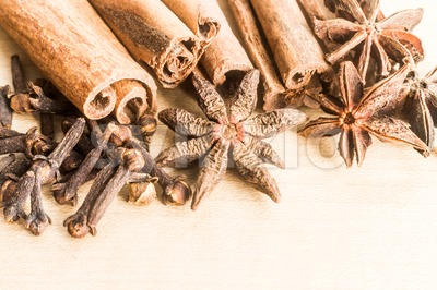 Group of popular spices consisting Cinnamon sticks, Cloves and Star Anise on wooden surface Stock Photo