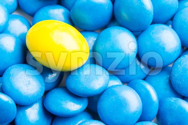 Concept of selective focus on yellow chocolate candy against heaps of blue candies in background