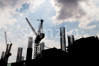Construction site with multiple tower cranes in silhouette Stock Photo
