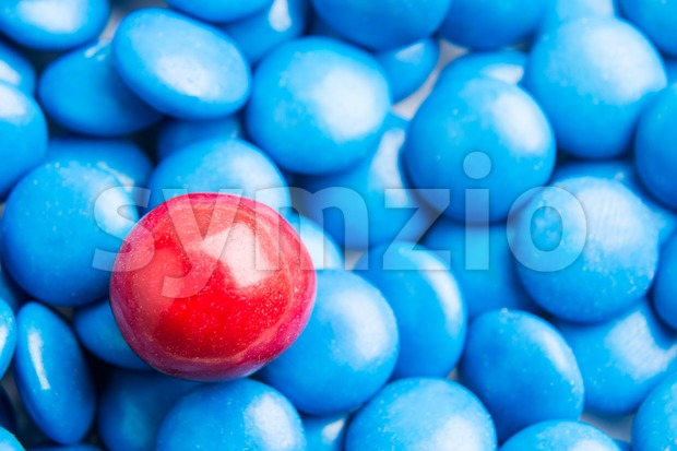 Concept of selective focus on red chocolate candy against heaps of blue candies in background