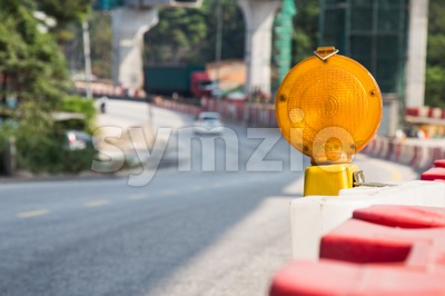 Construction site hazard warning light installed on road shoulders as safety caution Stock Photo