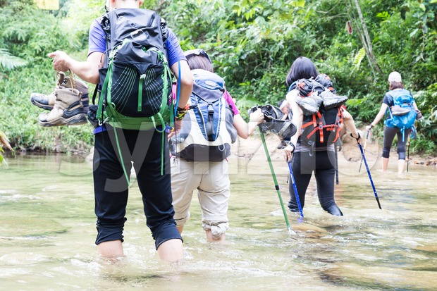 Group of people crossing river while hiking in a tropical forest