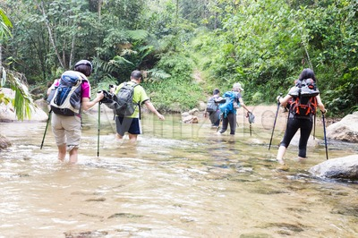 Group of people crossing river while hiking in a tropical forest Stock Photo