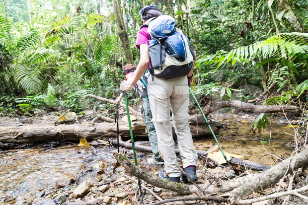 Two female hikers crossing river while hiking in a tropical forest Stock Photo