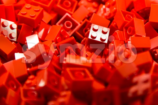 Pile of red color building blocks with selective focus and highlight on one particular block using available light. Stock Photo