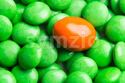 Focus on orange chocolate candy against heaps of green candies Stock Photo