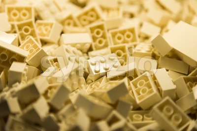 Pile of cream color building blocks with selective focus and highlight on one particular block using available light Stock Photo