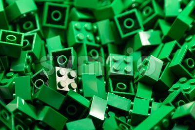 Pile of green color building blocks with selective focus and highlight on one particular block using available light. Stock Photo