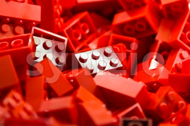 Pile of red color building blocks with selective focus and highlight on one particular block using available light Stock Photo