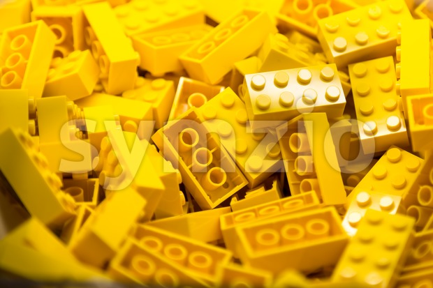 Pile of yellow color building blocks with selective focus and highlight on one particular block using available light. Stock Photo