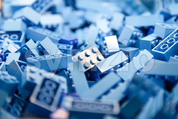 Pile of blue color building blocks with selective focus and highlight on one particular block using available light. Stock Photo