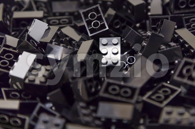 Pile of black color building blocks with selective focus and highlight on one particular block using available light. Stock Photo