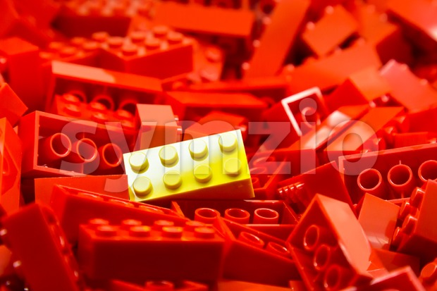 Pile of red color building blocks with selective focus and highlight on one particular yellow block using available light