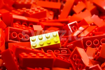 Pile of red color building blocks with selective focus and highlight on one particular yellow block using available light Stock Photo