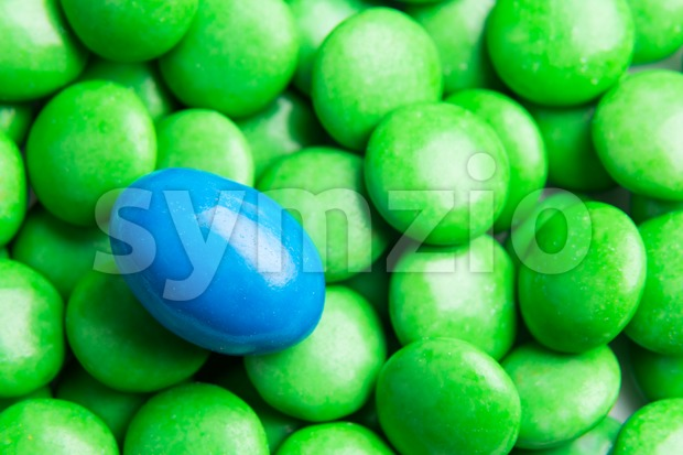 Concept of selective focus on blue chocolate candy against heaps of green candies in background