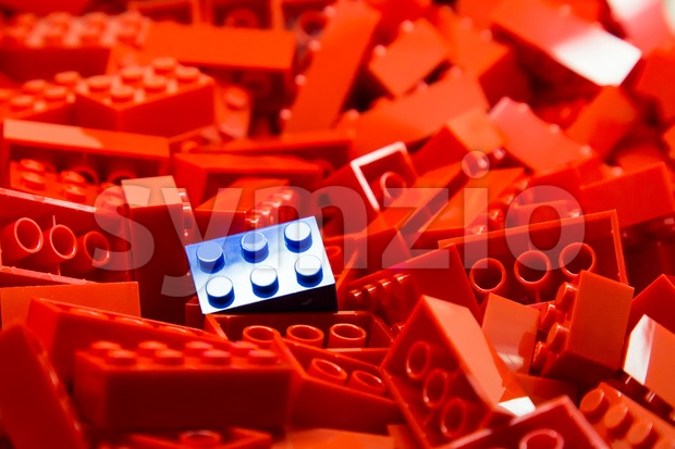 Pile of red color building blocks with selective focus and highlight on one particular blue block using available light. Stock Photo