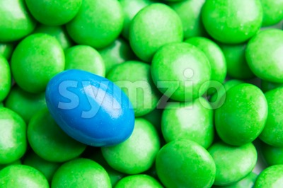 Focus on blue chocolate candy against heaps of green candies Stock Photo