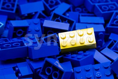 Pile of blue color building blocks with selective focus and highlight on one particular yellow block using available light. Stock Photo