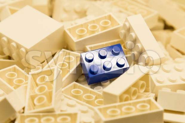 Pile of white color building blocks with selective focus and highlight on one particular blue block using available light. Stock Photo