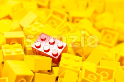 Pile of yellow color building blocks with selective focus and highlight on one particular red block using available light. Stock Photo
