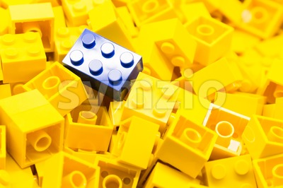 Pile of yellow color building blocks with selective focus and highlight on one particular blue block using available light. Stock Photo