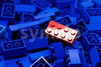 Pile of blue color building blocks with selective focus and highlight on one particular red block using available light. Stock Photo