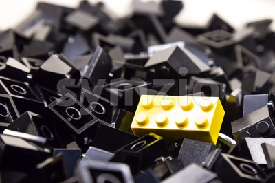 Pile of black color building blocks with selective focus and highlight on one particular yellow block using available light Stock Photo