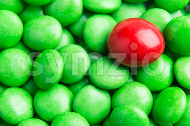 Concept of selective focus on red chocolate candy against heaps of green candies in background