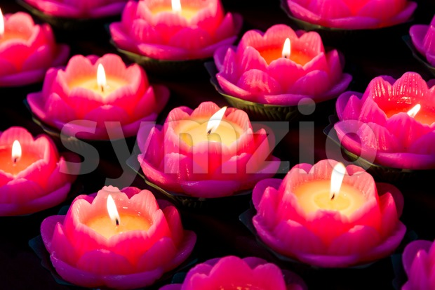 Lotus shaped candle lights used in Buddhist temple illuminate a dark surrounding Stock Photo