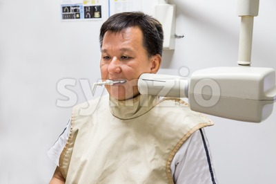 Man with radiation protection vest receiving dental X-Ray at a dental clinic Stock Photo