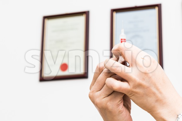 Medical doctor preparing injection syringe against backdrop of medical qualification certificates Stock Photo