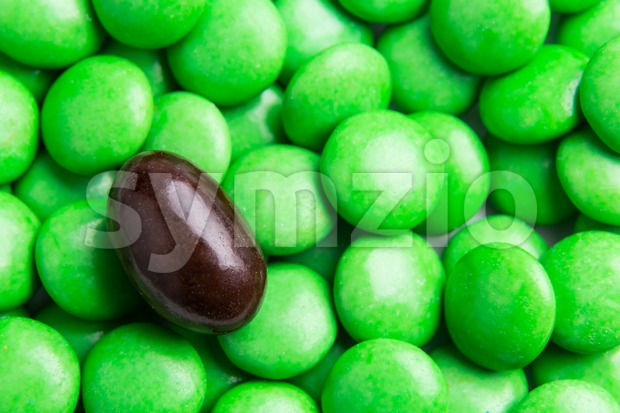 Concept of selective focus on brown chocolate candy against heaps of green candies in background