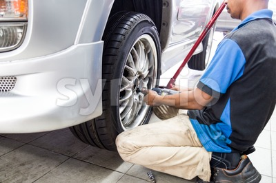 Mechanic detaching the wheel of a vehicle in a workshop Stock Photo
