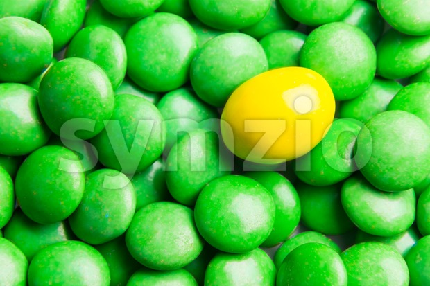 Focus on yellow chocolate candy against heaps of green candies Stock Photo