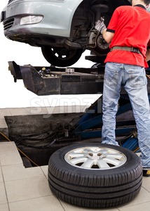 Mechanic repairing the wheel area of a vehicle in a workshop Stock Photo