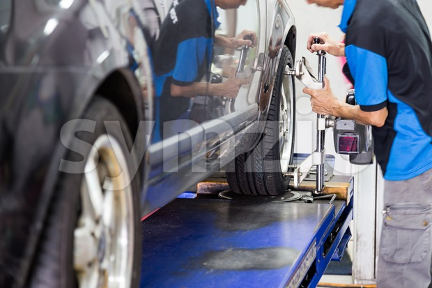 Mechanic fixing the wheel alignment device onto a car wheel. Focus is on the car wheel and wheel alignment device. Stock Photo