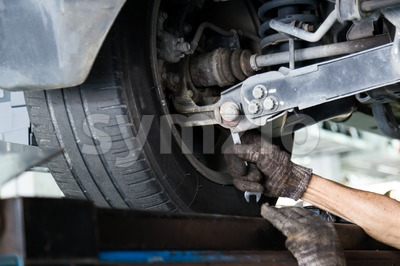 Mechanic adjusting the nut on the chamber during wheel alignment process Stock Photo