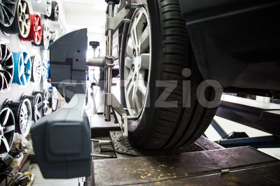 Closed up of an auto wheel that is undergoing wheel alignment Stock Photo