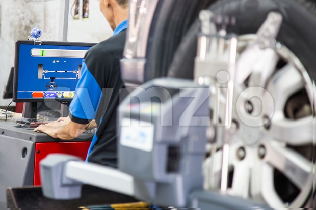 Mechanic adjusting the computer settings connected to the wheel alignment device Stock Photo