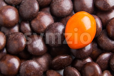 Focus on orange chocolate candy against heaps of brown candies Stock Photo