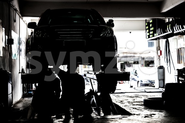 Silhouette image of mechanics inspecting cars suspended on platform in a very small and tight workshop Stock Photo