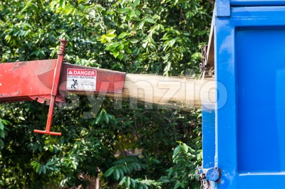 Wood chipper machine releasing the shredded green leafs and trunk into a truck Stock Photo