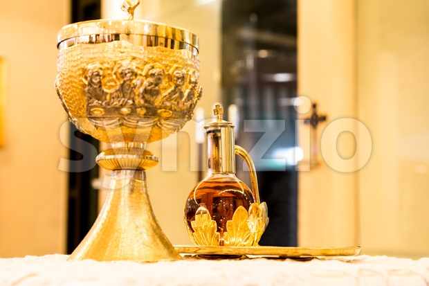 Catholics bread and wine in chalice with crucifix in background Stock Photo