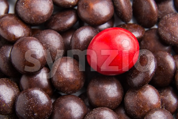 Concept of selective focus on red chocolate candy against heaps of brown candies in background